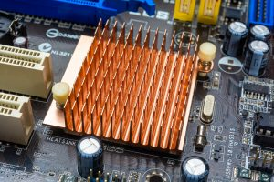 Close up view of copper heat sink or radiator on computer motherboard.