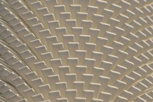 Pattern of white vanes on a heat dissipator or radiator. Part of utilities for a  northern town.
