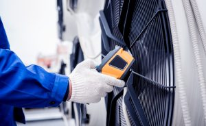 Technician uses a thermal imaging infrared thermometer to check the condensing unit heat exchanger