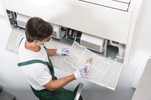 Young male technician cleaning air conditioner indoors